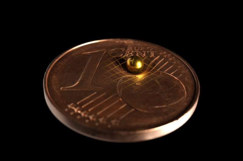 Sfera di oro usata per l'esperimento gravitazionale, comparata a una moneta da 1 centesimo di Euro. Crediti: Tobias Westphal / Arkitek Scientific