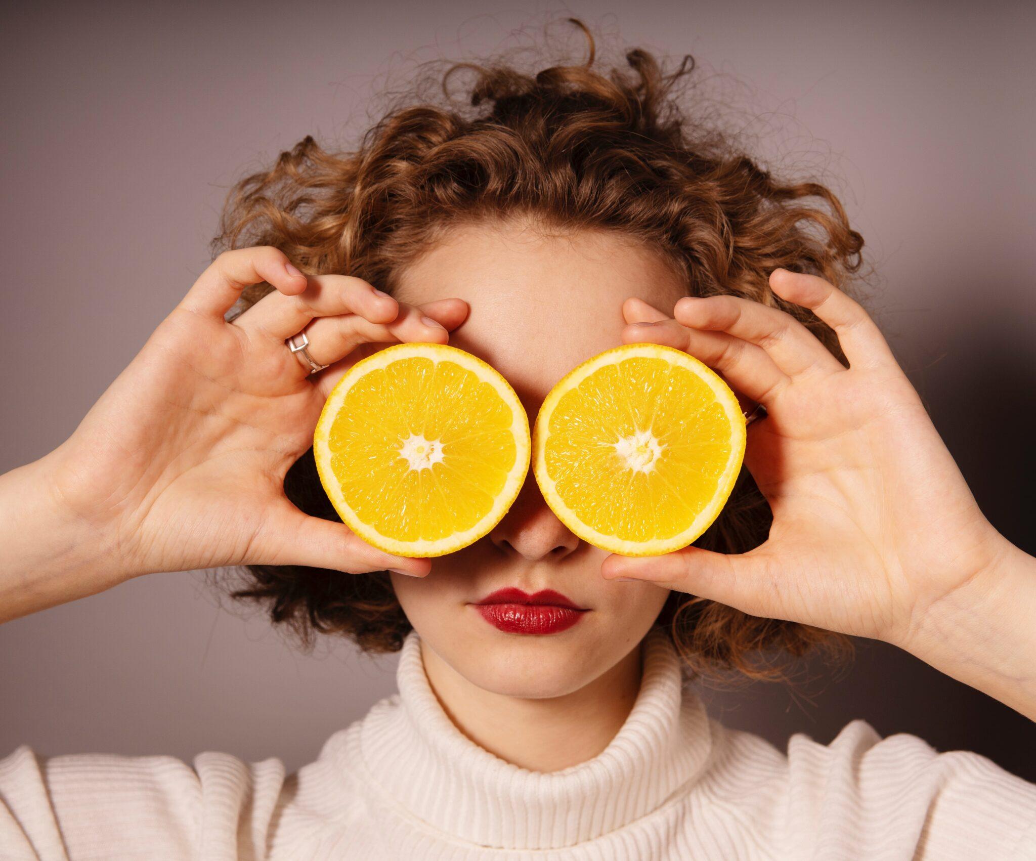 donna usa due fette di agrumi come occhiali