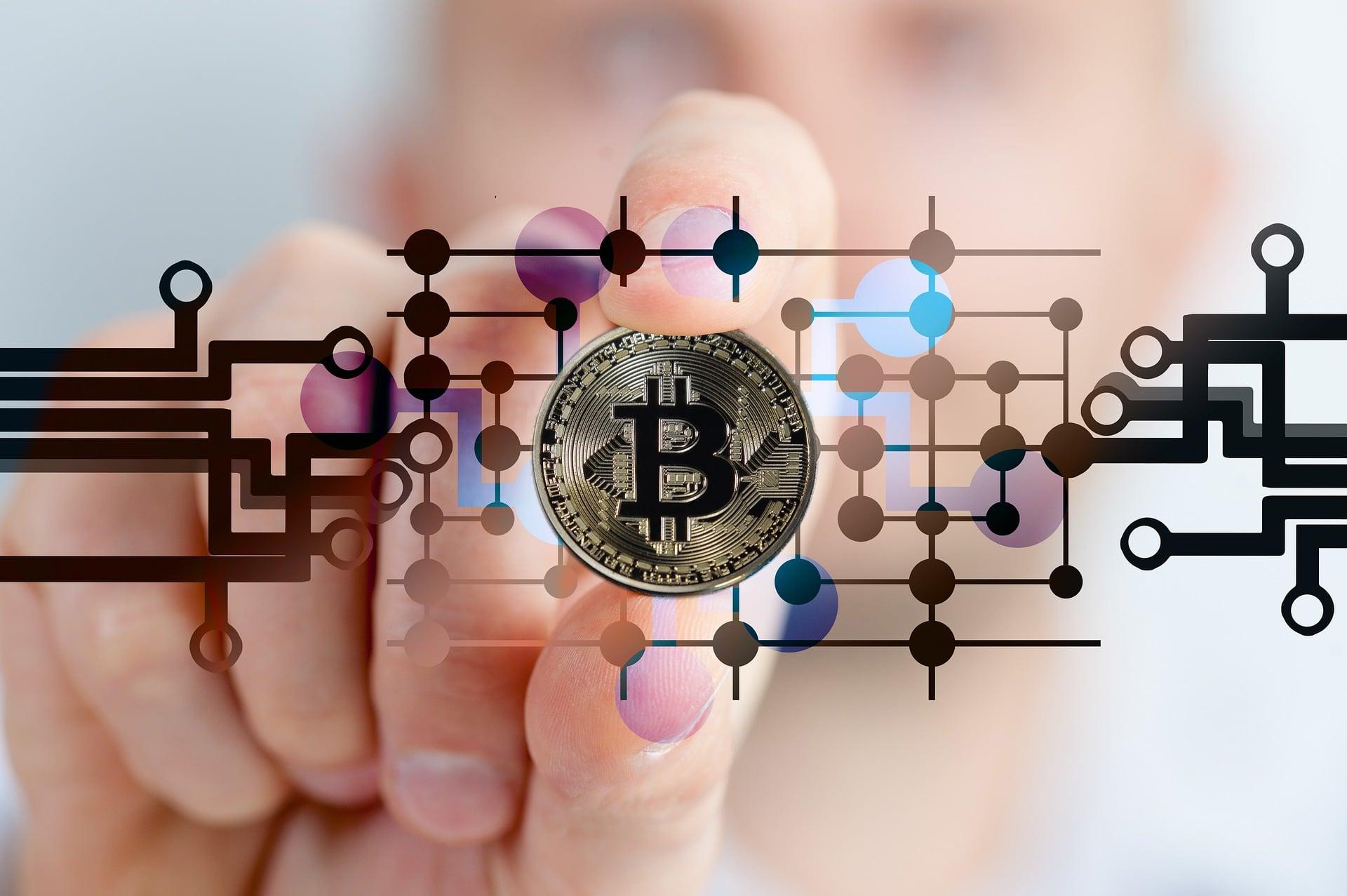 mano tiene un Bitcoin immerso in circuiti di microchip