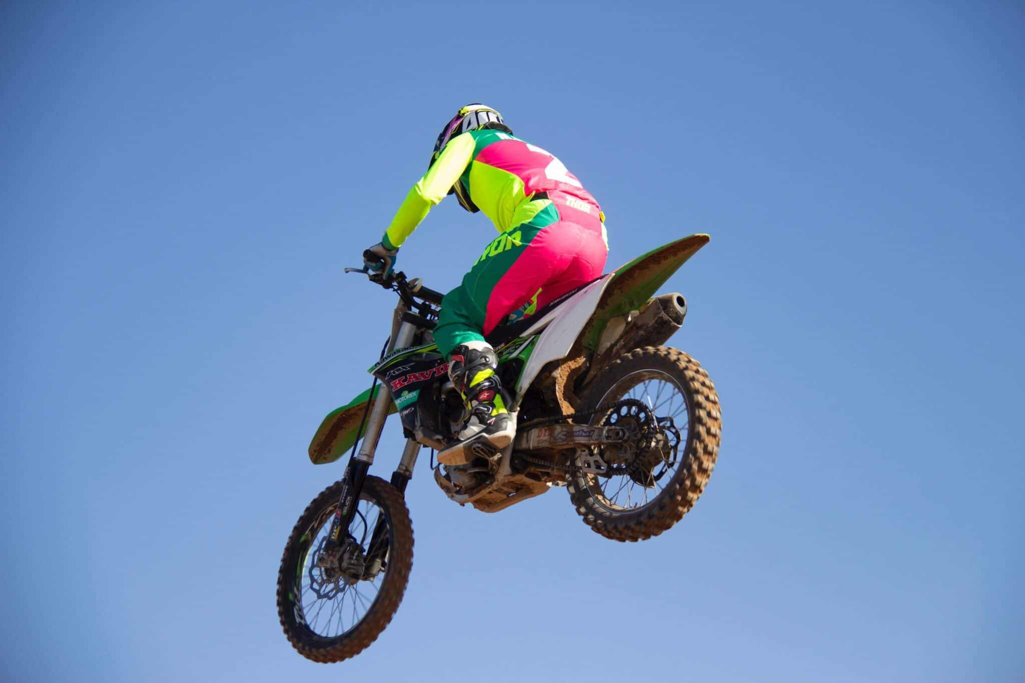 salto acrobatico moto sportiva su sfondo azzurro cielo