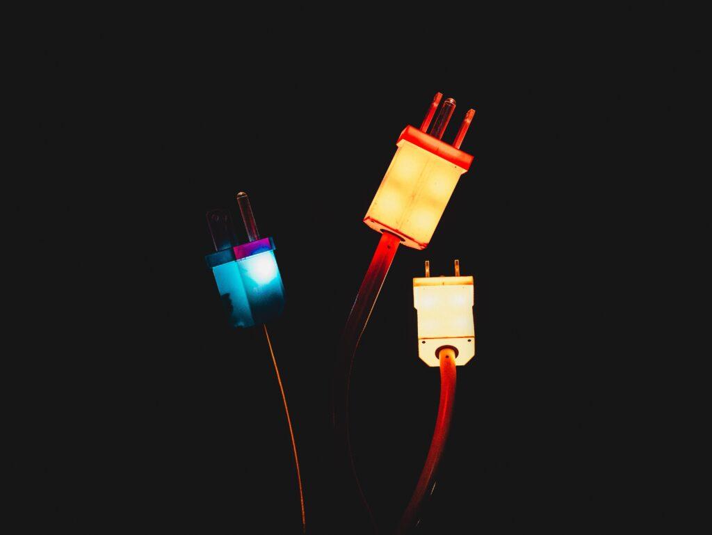 tre spine elettrice fluorescenti su sfondo nero per rappresentare la termoelettricità