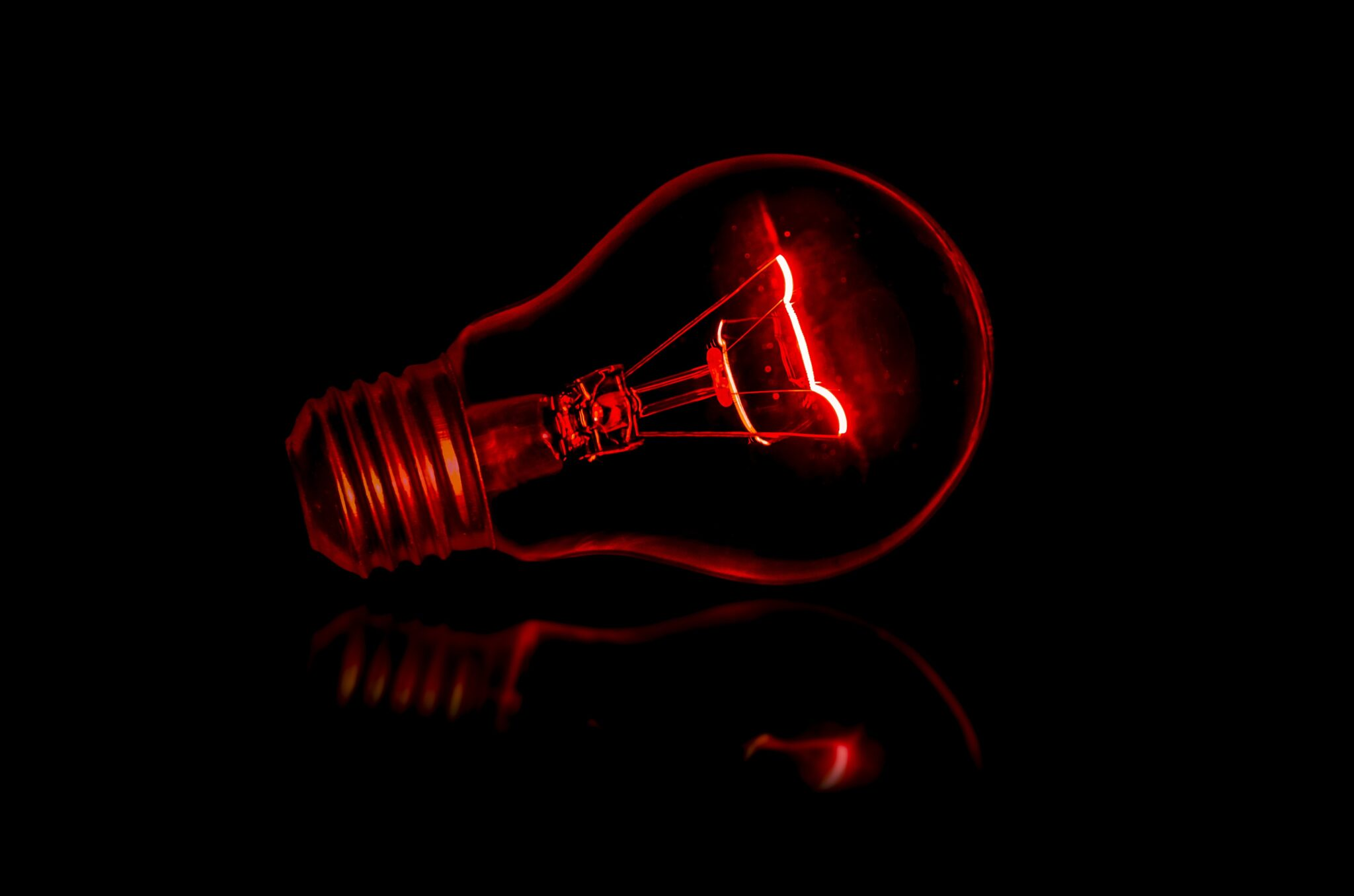 lampadina elettrica rossa su sfondo nero