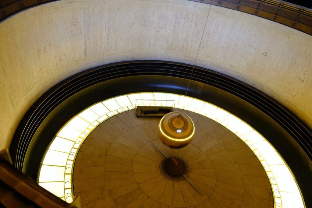 Foto di un pendolo oscillante davanti ad un grande orologio nel Griffith Observatory, Los Angeles, CA, USA