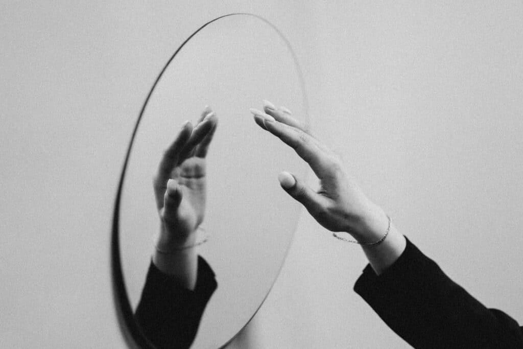 foto in bianco e nero di una mano che ta per toccare uno specchio e che si riflette in esso
