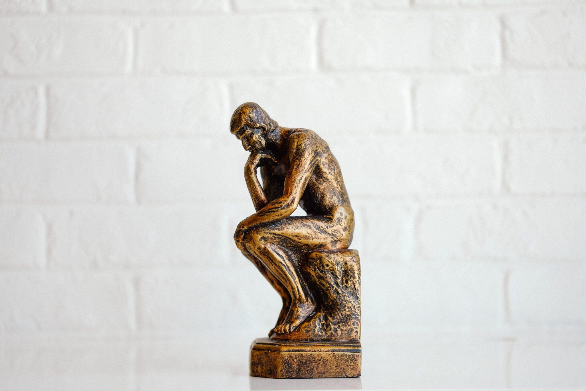 statua del pensatore fotografata di profilo su sfondo bianco